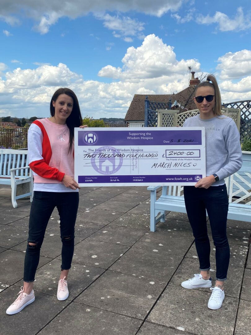 Allison left and Victoria right with a Friends branded cheque for £2,400 on the Hospice patio