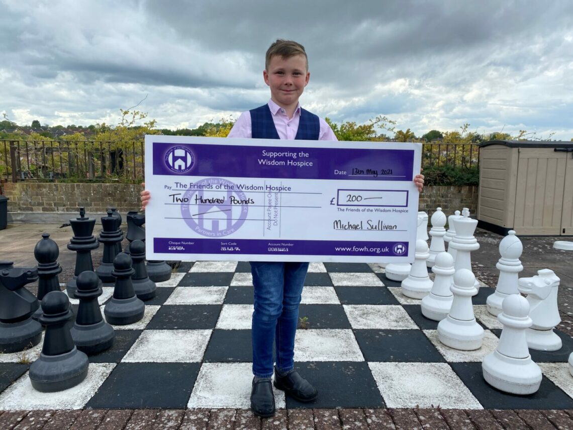Michael Sullivan smartly dressed on the hospice patio, infornt of the giant chess board with a large Friends presentation cheque for £200. Michael is smartly dressed in jeans.  a pink shirt and a tartan wasitcoat