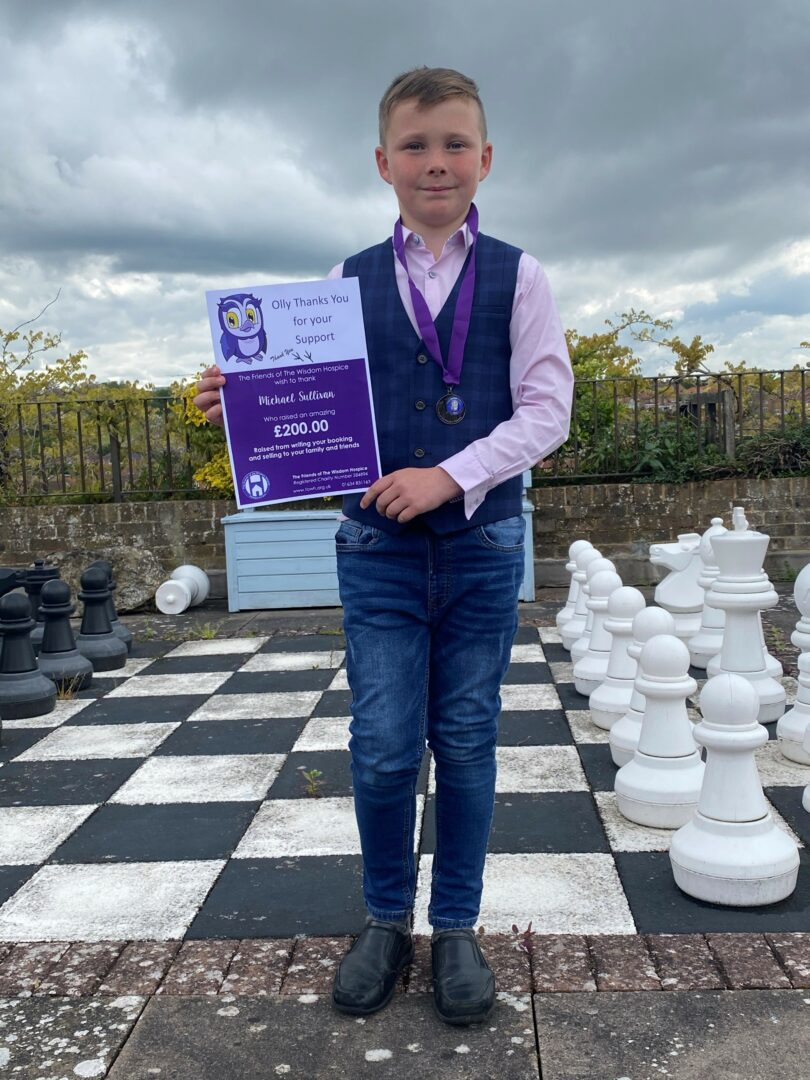 Michael Sullivan smartly dressed on the hospice patio, infornt of the giant chess board with his certificate of fundraising and his medal, Michael is smartly dressed in jeans.  a pink shirt and a tartan wasitcoat